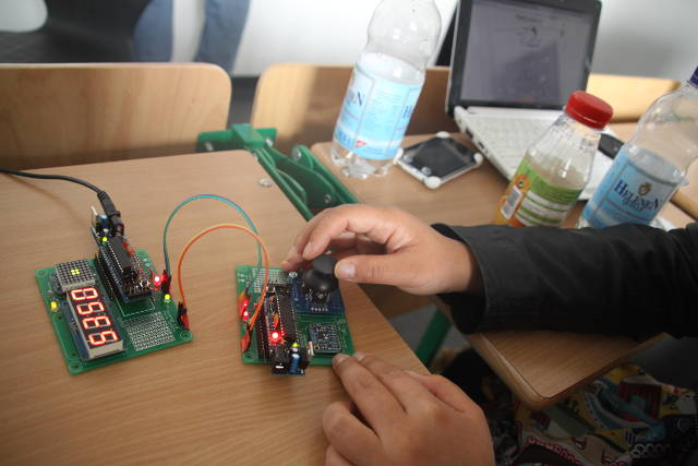 Aryeom tinkering with the devices to hack during the Reverse Engineering Workshop.